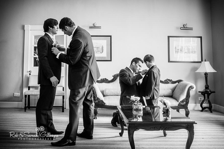 reportage image of groomsmen fixing buttonhole flowers