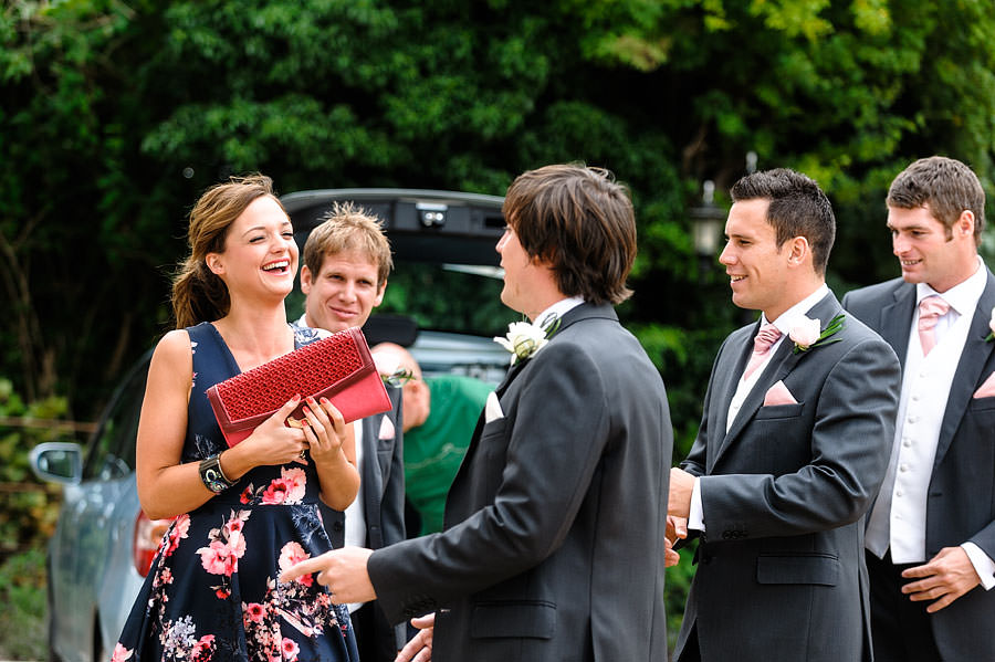 groom greeting female wedding guest