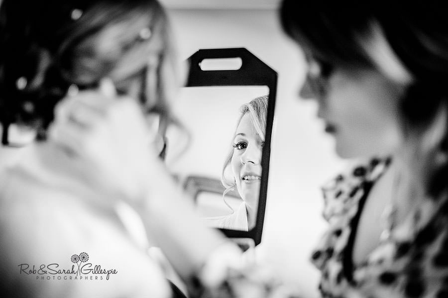 bride checks hair in mirror