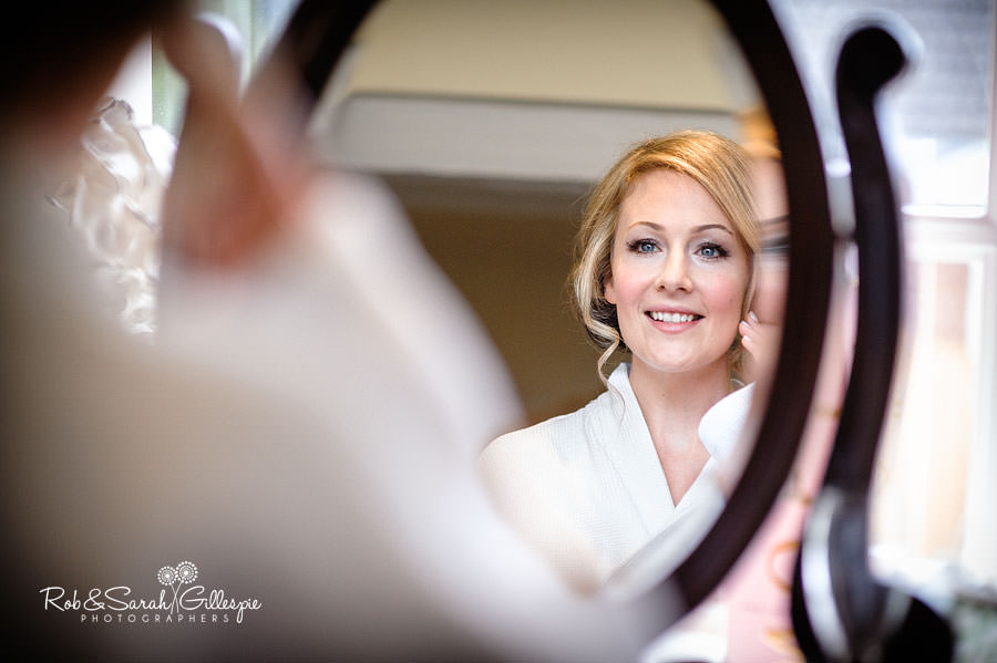 bride looks at herself in mirror