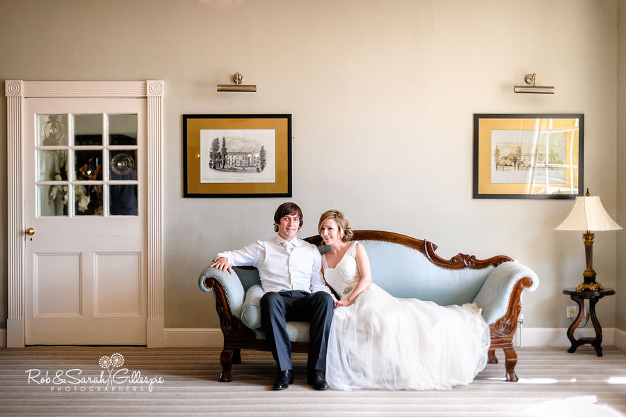 Bride and groom together on sofa at Warwick House