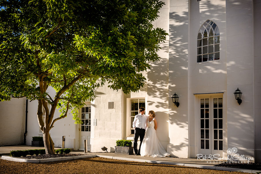 Bride and groom underneath tree at Warwick House in beautiful evening light