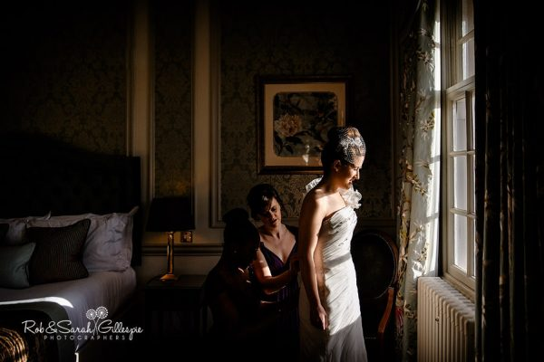 Bride preparing for wedding at Brockencote Hall in beautiful light