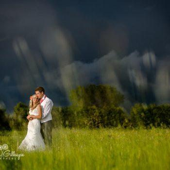 Bride & groom in green field with stormy sky
