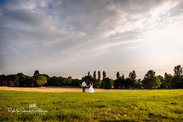 Bride and groom walk together within Hagley Hall grounds