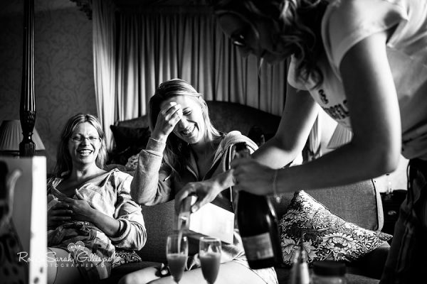 Bride and bridesmaids laughing while getting ready for wedding at Welcombe Hotel