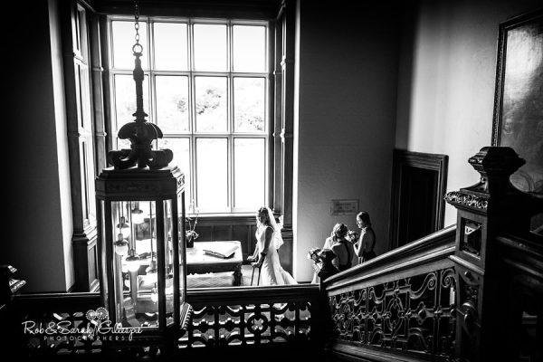 Bride and bridesmaids on staircase at Welcombe Hotel in Warwickshire