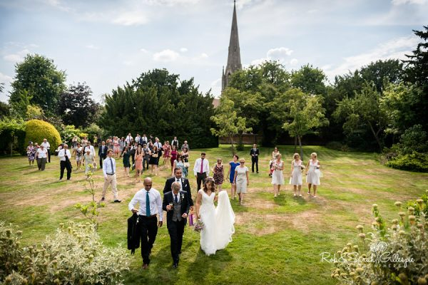 Bride, groom and wedding guests walk in grounds at Sherbourne Park