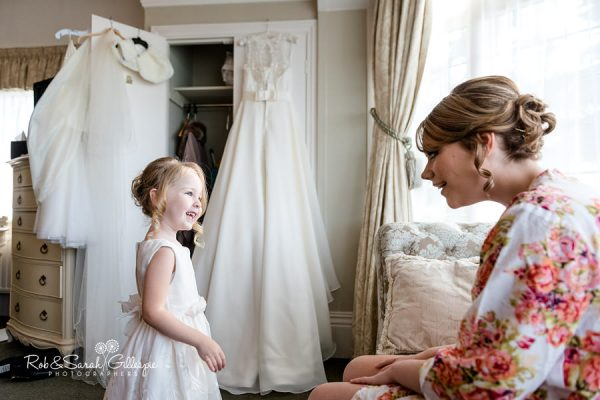 Bride and flowergirl prepare for wedding at Nuthurst Grange