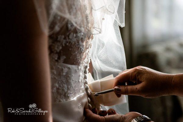 Bride has dress fastened at Nuthurst Grange wedding