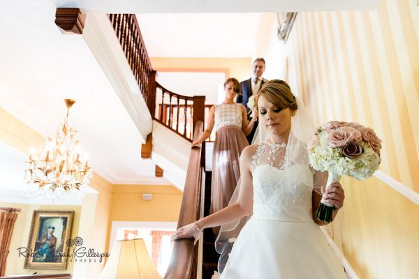 Bride and bridesmaids on staircase at Nuthurst Grange