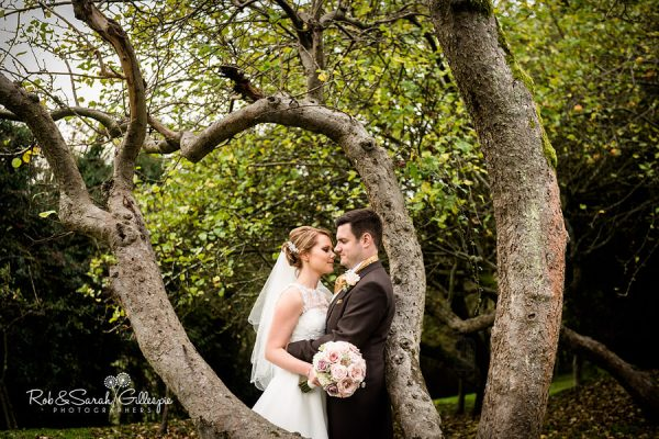Bride and groom amongst trees at Nuthurst Grange