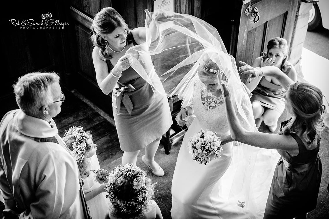 Black and white photograph of bride's veil being adjusted by bridesmaids before the service beings.