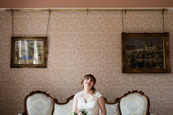 Bride laughing while sitting on antique couch at Highbury Hall