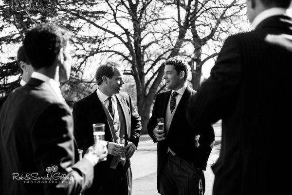 Groom chats with friends at Malvern College wedding