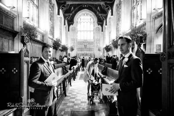 Ushers hand out order of service to wedding guests at Malvern College wedding