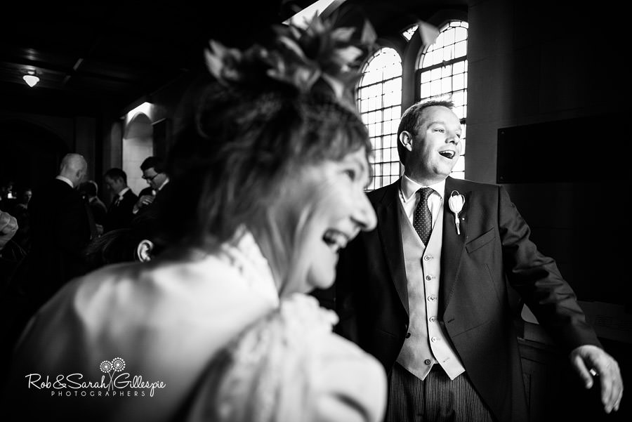 Groom welcomes guests to wedding at Malvern College chapel
