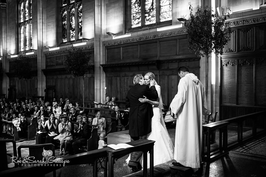 Bride and groom first kiss during wedding at Malvern College Chapel