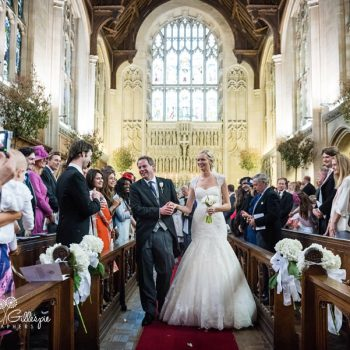 Newly married couple leave Malvern College Chapel after wedding cerremony