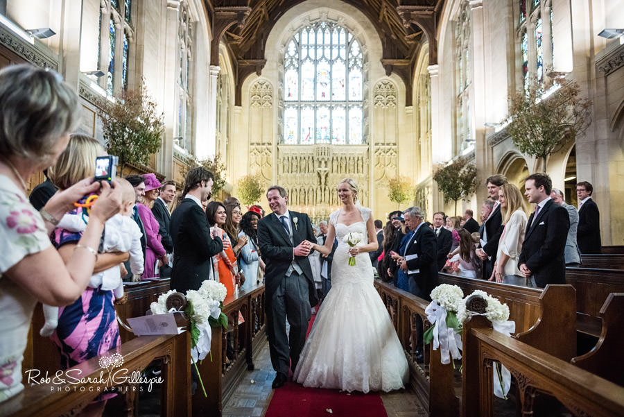 Bride and groom walk down the aisle inside Malvern College chapel