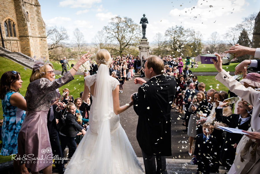 Bride and groom with guests throwing confetti at Malvern College