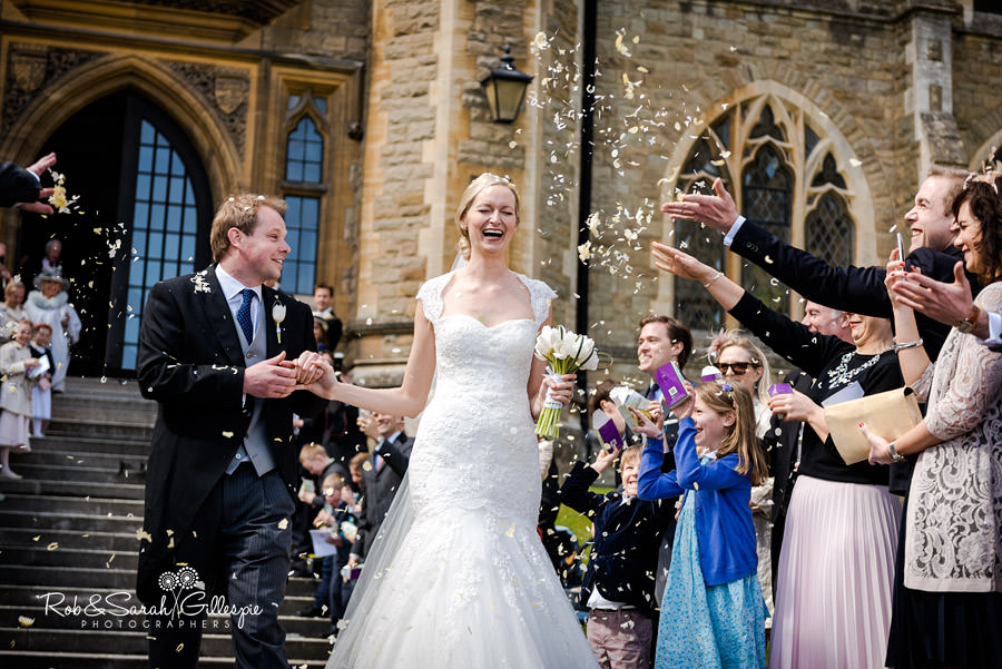 Bride laughs as confetti is thrown over her at wedding