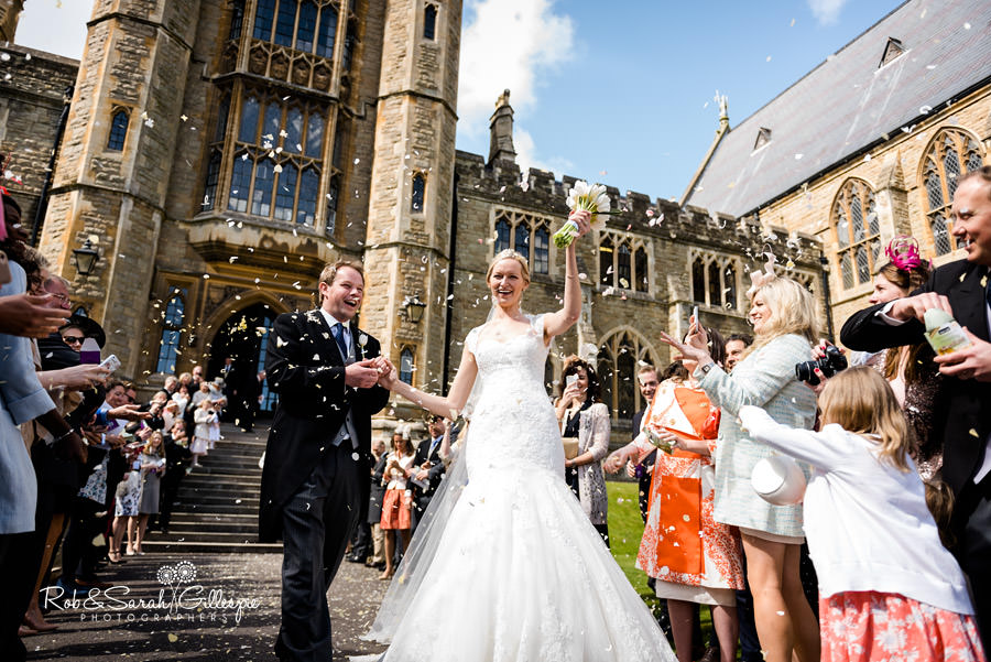 Wide angle image of bride and groom surrounded by confetti at Malvern College