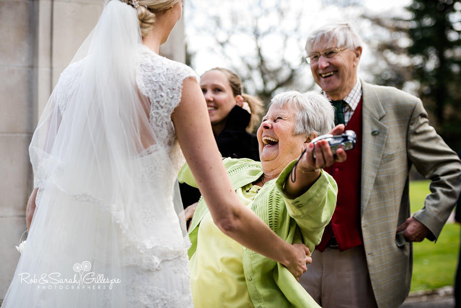 Wedding guest hugs bride with big smile on her face