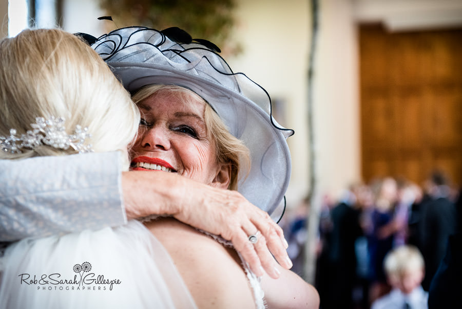 Bride hugged by mother at Malvern College wedding