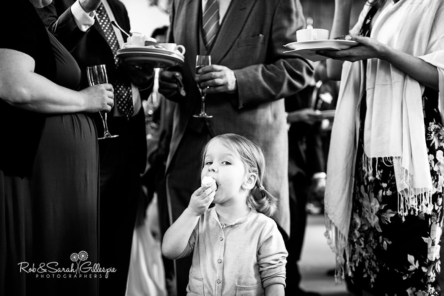 Little girl eats cake at wedding
