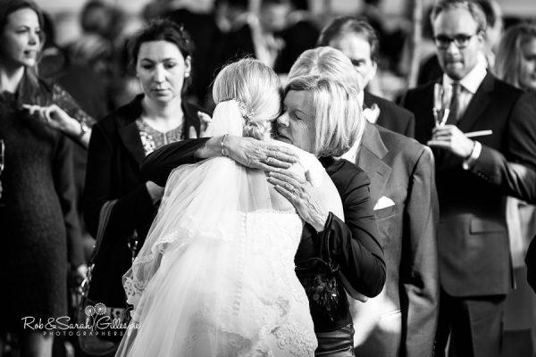 Wedding guests hug bride at Malvern College wedding