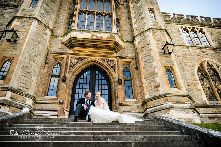 Happy bride and groom sitting on steps at Malvern College