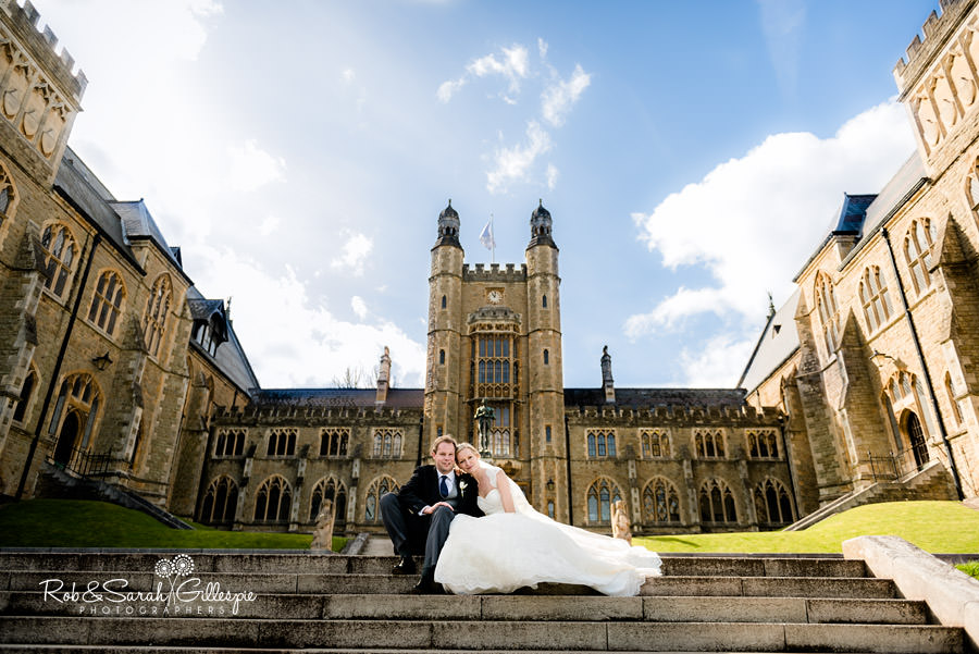 Dramatic wide angle of Malvern College with bride and groom sitting on steps together