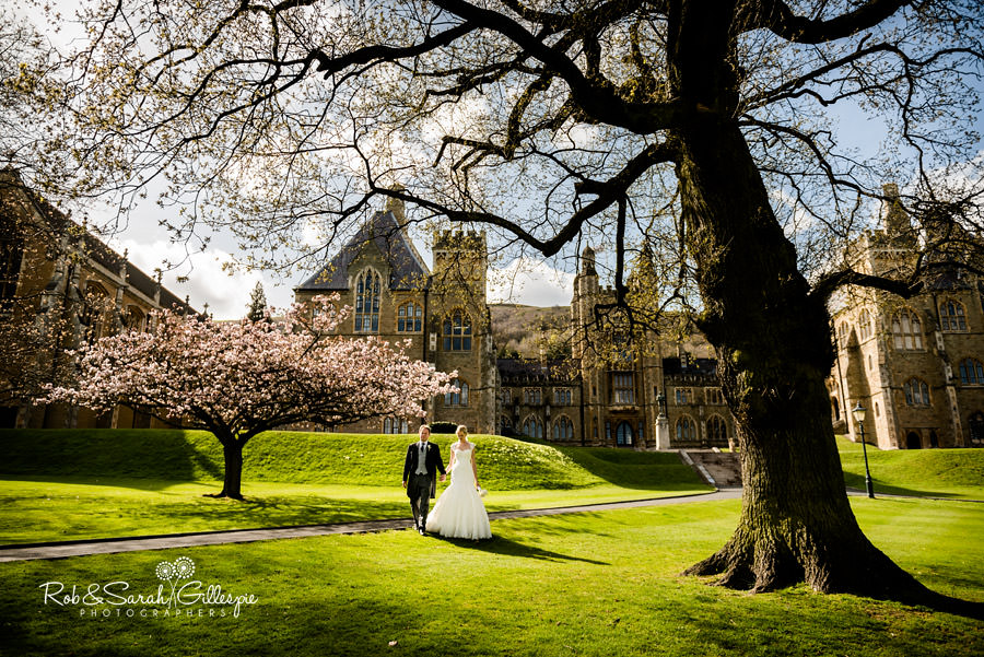 Malvern College grounds with bride and groom walking hand in hand