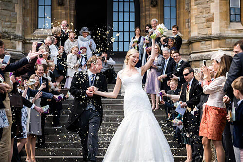 Bride and groom walk through confetti throw at Malvern College wedding