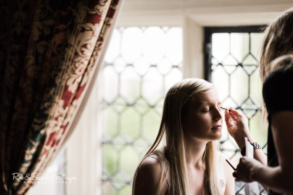 Bride having makeup in beautiful window light at Coombe Abbey