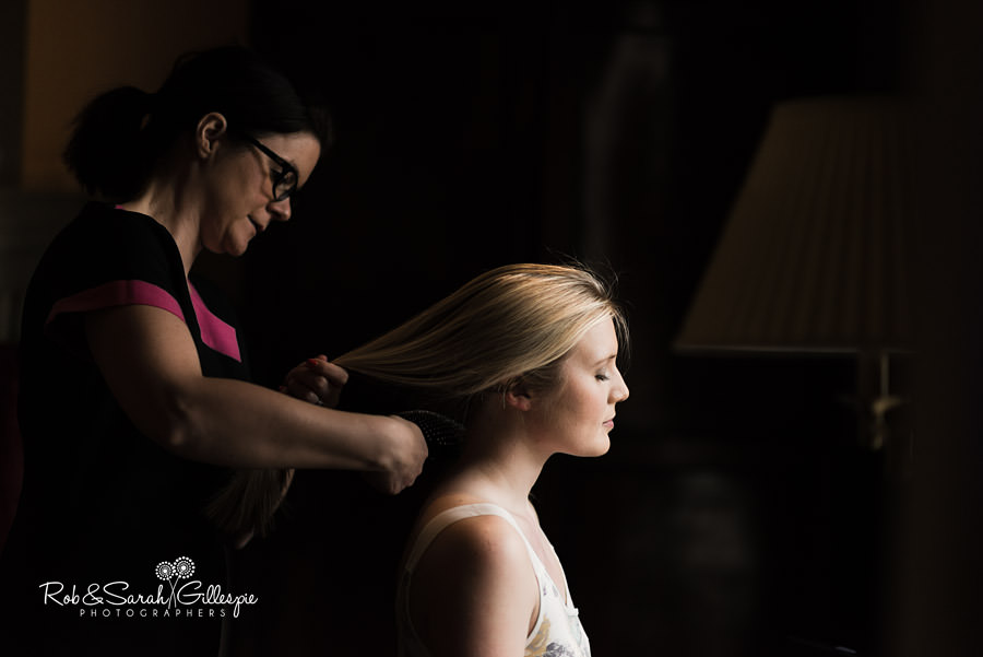 Bride having hair styled before wedding in beautiful window light