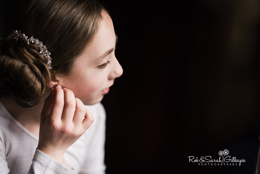 Bridesmaid putting earrings on before wedding