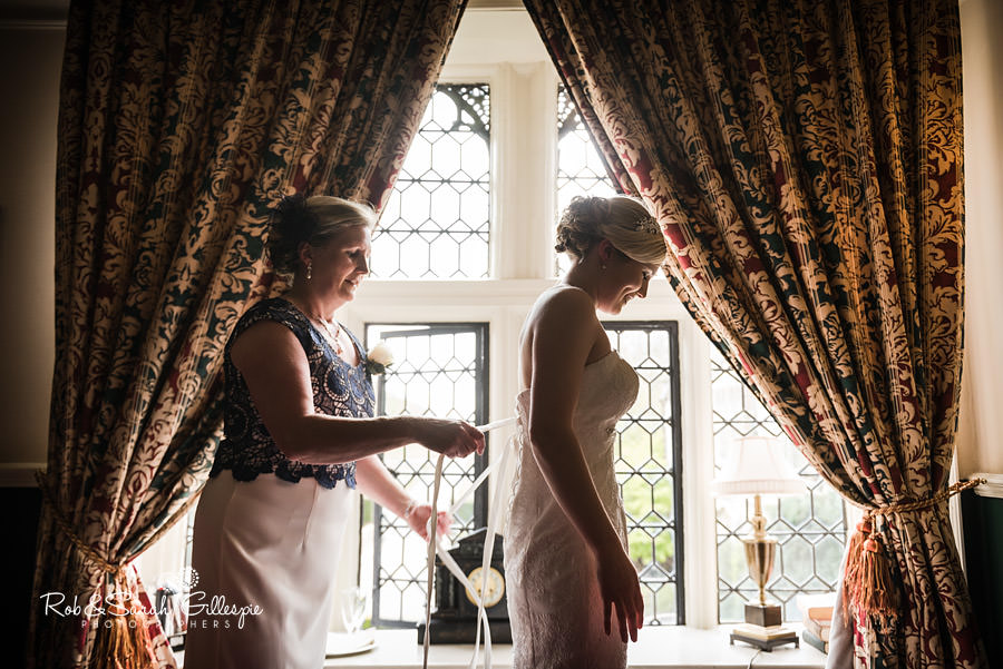 Bride having dress fastened in window light at Coombe Abbey