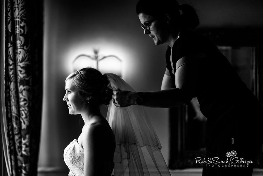 Bride having veil adjusted in beautiful window light