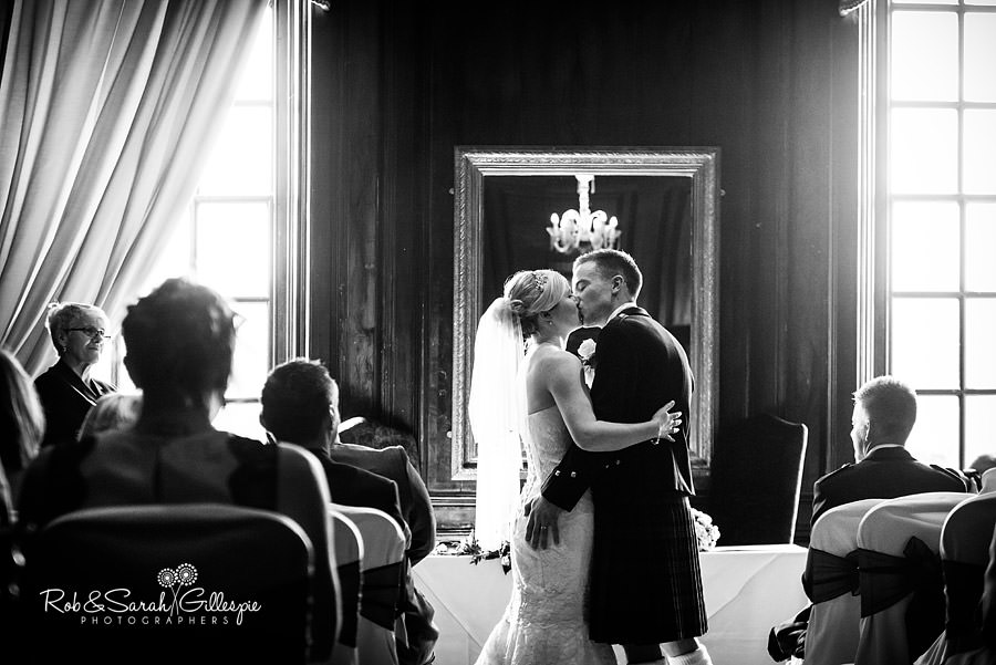 First kiss during wedding ceremony in Walnut Room at Coombe Abbey