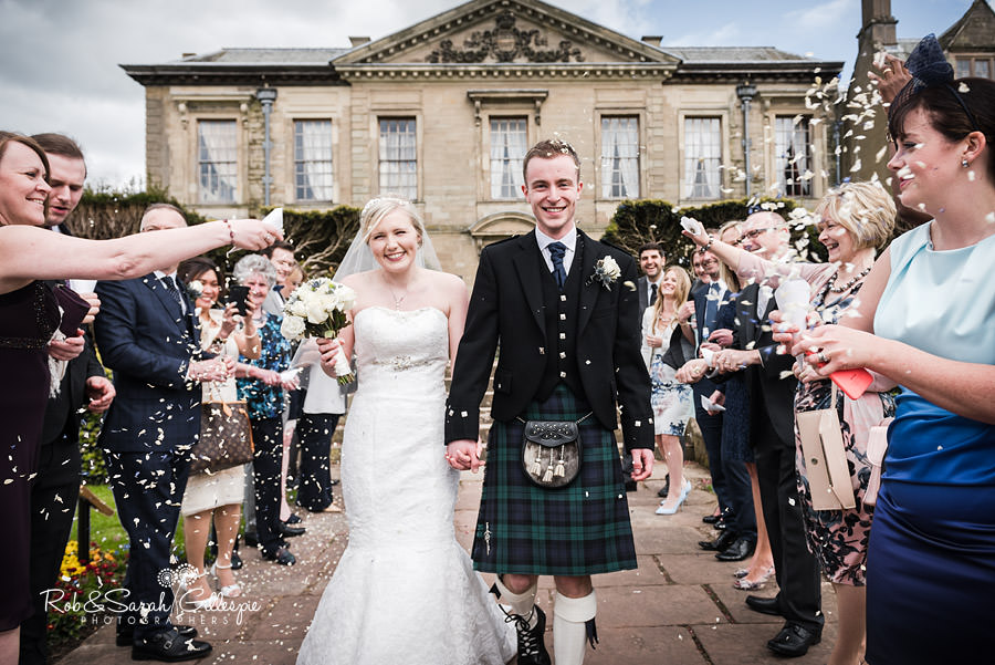 Bride and Groom walk through confetti outside Coombe Abbey in Warwickshire