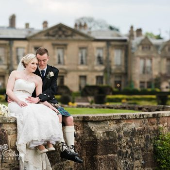 Bride & Groom sitting on wall in grounds at Coombe Abbey