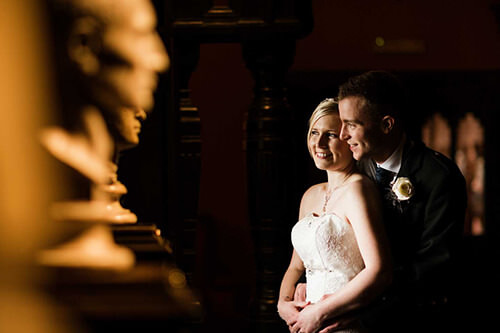 Bride and groom together by statues at Coombe Abbey
