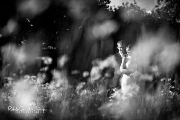 Bride and groom in long grass at Wethele Manor
