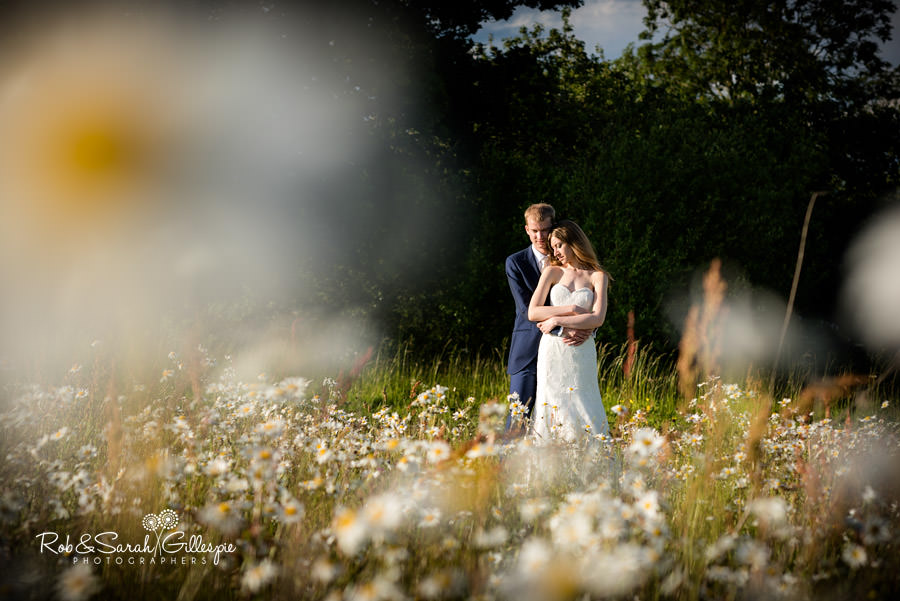Bride and groom together in wild flower field at Wethele Manor