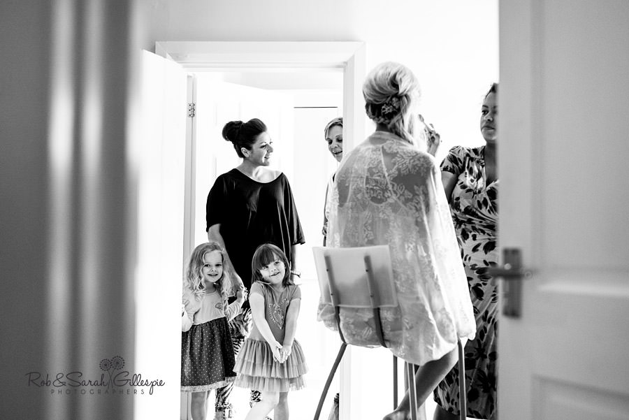 Bride preparing for her Delbury Hall wedding while flowergirls look on
