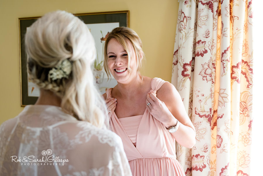 Bride and bridesmaid laughing at Delbury Hall prior to wedding