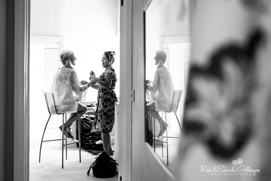 Bride laughing with makeup artist by Rob & Sarah Gillespie Photographers