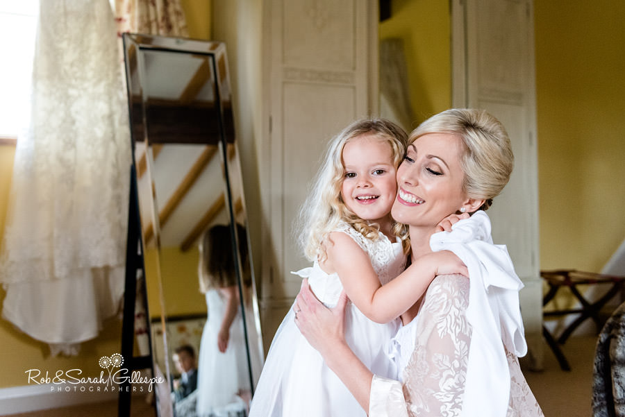 Bride hugs flowergirl in beautiful light at Delbury Hall Coachhouse